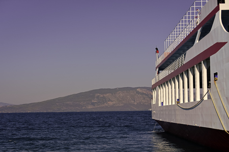 Part of big cruise liner in sea at sunny day. Cruise ship sailing from port. Skyline with mountains and ocean, horizon, beautiful landscape with clean blue sky, copy space.