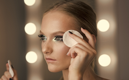 Woman use cotton pad for cleaning face skin. Woman remove makeup with cotton pad. Beauty model with fresh face skin, skincare. Makeup application or removal. Skincare, treatment and therapy. Stock Photo