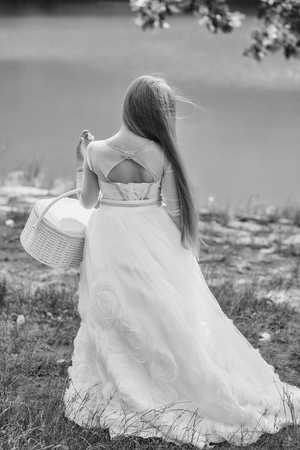 small girl kid with long blonde hair in prom princess white dress standing sunny day outdoor near water with basket Stock Photo