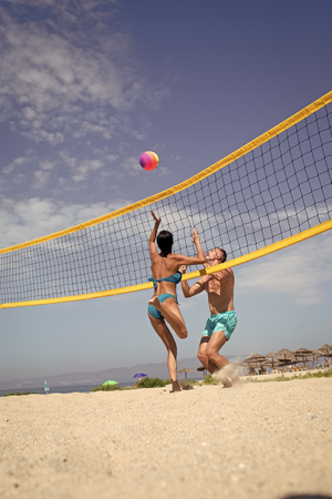 Woman and man fit, strong, healthy, doing sport on beach. Beach volleyball concept. Couple have fun playing volleyball. Young sporty active couple beat off volley ball, play game on summer day.