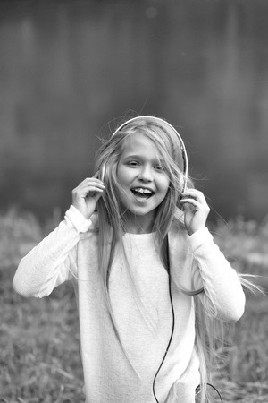 small girl kid with long blonde hair and pretty smiling happy face in white with headphones on head standing outdoor near water on green natural background.