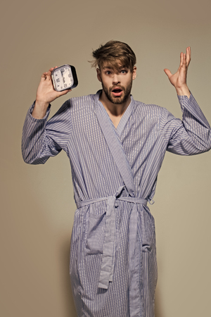 Macho with surprised face in dressing gown. Man with alarm clock on grey background. Time, routine, deadline. Morning, wake up concept. Stock Photo