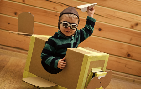 Air mail delivery, aircraft construction. Little boy child play in cardboard plane, childhood. Kid, pilot school, innovation. Pilot travel, airdrome, imagination. Dream career adventure education