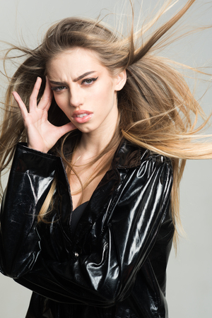 Lady sexy in slicker or raincoat suffers headache. Girl with long hair wears black cloak, grey background. Woman attractive on painful face touches temples. Headache concept.