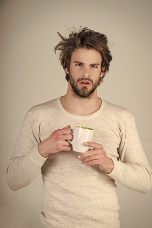 Man with disheveled hair drink mulled wine. Imagens