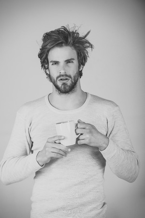 Man with disheveled hair drink mulled wine. Stock Photo
