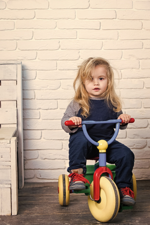 Baby cyclist with long blond hair on white brick wall Stock Photo