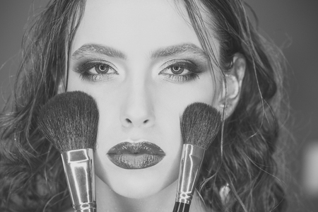 Beauty woman with makeup brushes, visage. Beauty model apply powder on face Stock Photo