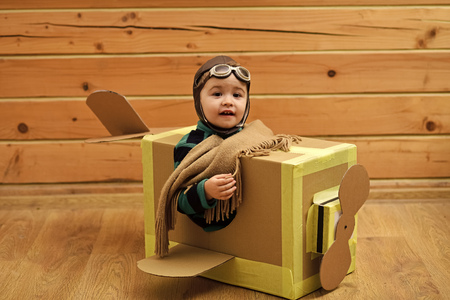 Little dreamer boy playing with a cardboard airplane