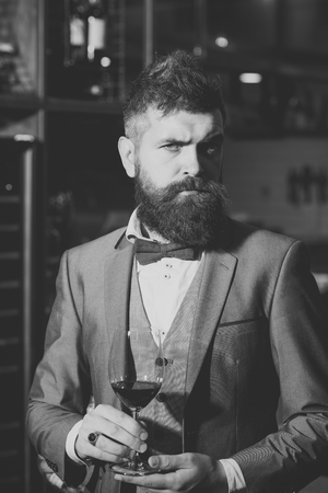 Confident winemaker in romantic atmosphere of cigar club. cigar club, serious winemaker with glass in business suit