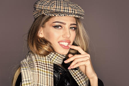 Sexy lady in fashionable outfit, close up. Woman on seductive face with make up with checkered accessories. Fashion accessories concept. Girl with long hair wears plaid kepi, scarf.