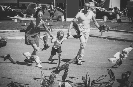 Happy family spend time together, urban background. Parents with son running near doves, chasing pigeons, happy boy with smiling face. Mother and father with their child. Family walk concept.