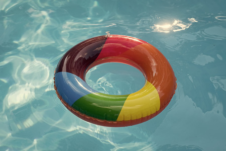 Summer vacation and travel to ocean, Bahamas. Maldives or Miami beach. Relax in spa luxury swimming pool. colorful swim ring or lifebuoy. inflatable ring float in pool blue water. Banco de Imagens