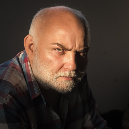 Man with grey beard, frown brows on serious face 스톡 콘텐츠