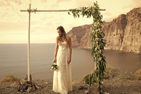 Pretty bride in white dress with wedding bouquet under arch Stock Photo