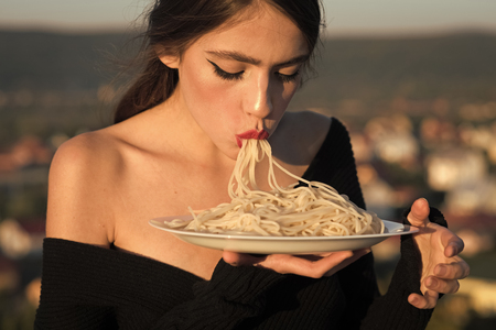recipe of traditional italian food. recipe of pasta in hands of woman eating macaroni