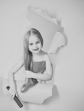 Little girl in vintage dress, prom. little girl with long hair hold brush. Stock Photo