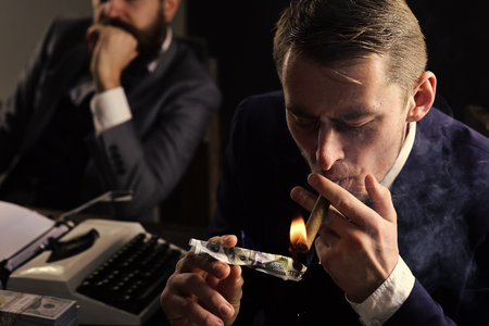 Man lighting cigar from burning banknote. Squander concept. Businessmen in suits sit at table with typewriter and money in dark interior, defocused. Businessman smoking cigar at business meeting. Zdjęcie Seryjne - 100824719