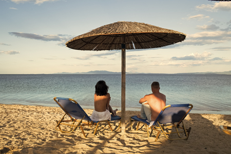 Couple on vacation or honeymoon. Man and woman topless enjoy view on sea, rear view. Honeymoon concept. Couple in love at sea resort sits on loungers under umbrella on sand beach.
