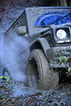 Black crossover driving with cloud of smoke through dirt, close up. Dirty offroad car overcomes obstacles in forest area. SUV covered with mud stuck. 4x4 racing concept