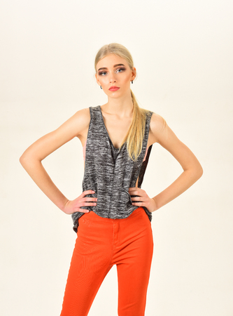 Skinny model with thick eyebrows and neat ponytail wearing melange gray sleeveless blouse and bright orange pants isolated on white background.
