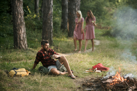 Picnic at sunny meadow. Two girls wandering in woods while thoughtful man is sitting on grass. Brutal bearded man drinking coffee or tea by campfire. Friendship and nature concepts.