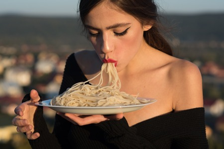 Recipe of pasta in hands of woman eating macaroni