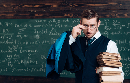 Young professor holding pile of books looking over his glasses. Aristocrat scholar in elite college. Stock Photo