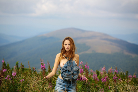 Pretty cute sexy naked woman or girl in blue jeans shorts with bare chest and long hair stands straight outdoor on beautiful landscape in field with bag Stock Photo