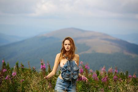 Donna o ragazza abbastanza carina in pantaloncini di jeans blu con petto e capelli lunghi sta dritto all'aperto sul bellissimo paesaggio in campo con la borsa