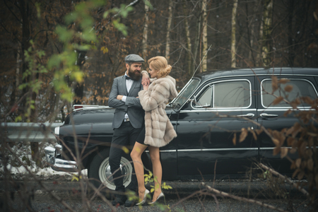 Couple in love on romantic date. Retro collection car and auto repair by mechanic driver. Travel and business trip or hitch hiking. Bearded man and sexy woman in fur coat. Escort of girl by security Stock fotó