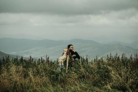 Couple romantique de jolie fille avec poitrine et bel homme barbu amoureux embrasser sur la falaise le jour d'été sur les sommets des montagnes et le ciel