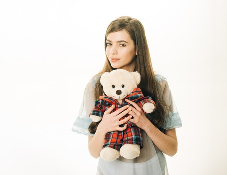 Girl with plush bear toy wishes sweet dreams.