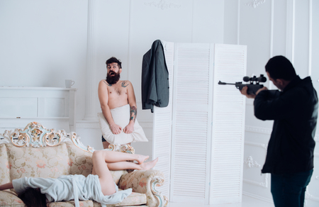 Man with beard naked, his wife on sofa, scared, shocked at gunpoint, interior background.