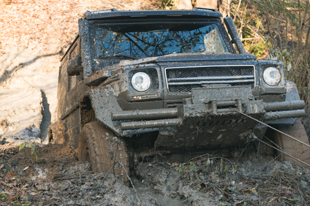 SUV is pulled out from puddle of mud by car winch. Crossover in dangerous situation. Dirty offroad car stuck in deep rut with nature on background. 4x4 racing concept. Banco de Imagens