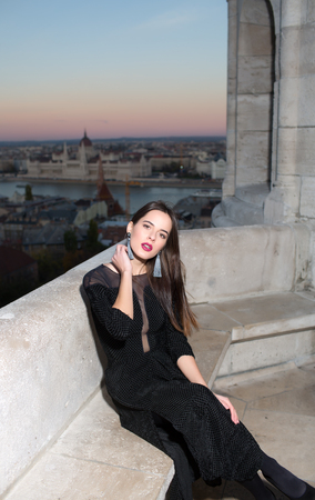 City view with princess in celebrity style. Girl with glamour makeup. Sexy girl in elegant dress. Fashion and beauty of business lady. Luxury woman in evening dress.