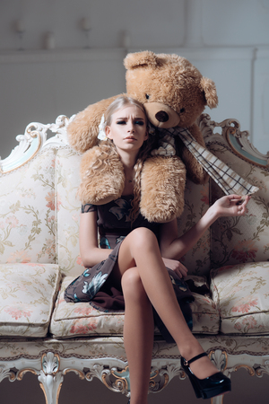 Young spoiled aristocrat sitting on vintage sofa. Blond lady playing with her huge teddy bear. 免版税图像
