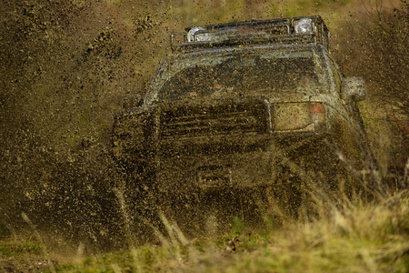 Splash of dirt under SUV on countryside road. Cross country rallying or rally raid on autumn field. Off road car takes part in racing on nature background. Extreme and four wheel drive concept