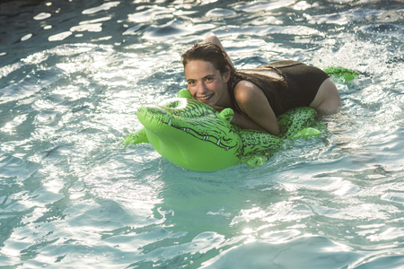 Beautiful woman in water with green Inflatable crocodile