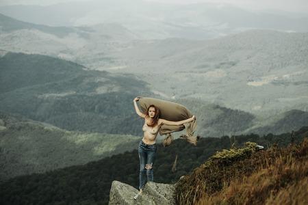 Hübsches Modell des hübschen Mädchens mit langen Haaren und Brust in Jeans mit Decke steht am Hang im Sommer auf Bergen, die mit Wald und Himmel bedeckt sind