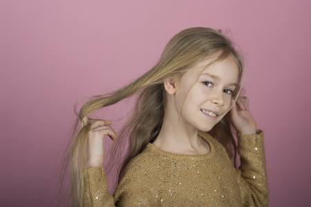 Pretty joyful young girl with long hair on pink background. Lovely sweet moments of little princess, pretty friendly child having fun to camera