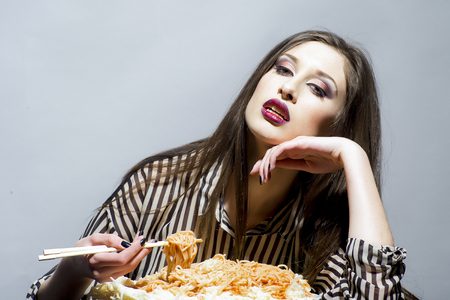 Hungry girl have italian food meal. Hungry woman eat spaghetti with chopsticks. Archivio Fotografico - 101250275