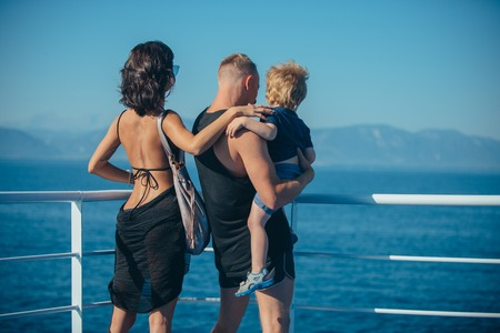 Summer vacation of happy family. Mother and father with son look at sea on beach. Family travel with kid on mothers or fathers day. Child with father and mother. Love and trust as family values