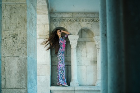fashion and beauty salon. girl in indian style dress in castle. Sexy girl in long dress with brunette hair. Fashion model or princess has romantic mood. Woman at stone ancient column in summer.