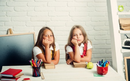 School time of girls. Back to school and home schooling. Little girls eat apple at lunch break. Friendship of small sisters in classroom at knowledge day. bored school kids at lesson in september 1.