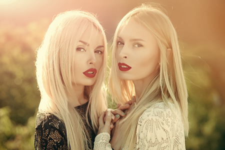 Two women with red lips and long blond hair Stockfoto