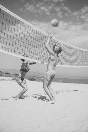 Beach volleyball concept. Couple have fun playing volleyball. Young sporty active couple beat off volley ball, play game on summer day. Woman and man fit, strong, healthy, doing sport on beach Stockfoto