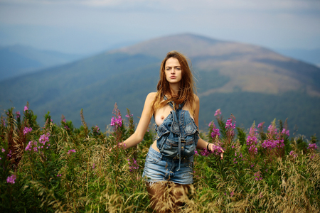 Pretty cute sexy naked woman or girl in blue jeans shorts with bare chest and long hair stands straight outdoor on beautiful landscape in field with bag Standard-Bild