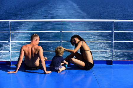 Summer vacation of happy family. Mother and father with son in sea on yacht. Family travel with kid on mothers or fathers day. Love and trust as family values. Child with father and mother.