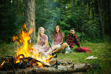 Happy friends having picnic in woods. Cheerful youngsters enjoying summer evening near campfire, weekend in countryside. Фото со стока